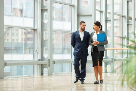 Businessman and businesswoman walk together and talk about business holding coffee in hand