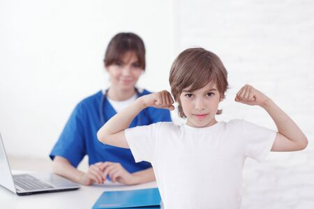 Healthy child showing muscles at pediatrician office female doctor on background