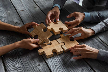Business people team sitting around meeting table and assembling wooden jigsaw puzzle pieces unity cooperation ideas concept