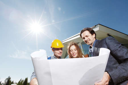 Worker shows construction plan to young couple outside house under construction sun in shining