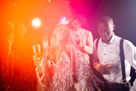 People having fun at 80s retro style party. People wearing costumes drinking champagne and dancing on dancefloor at nightclub in golden confetti