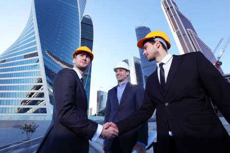 Investor and contractor shaking hands, view from below