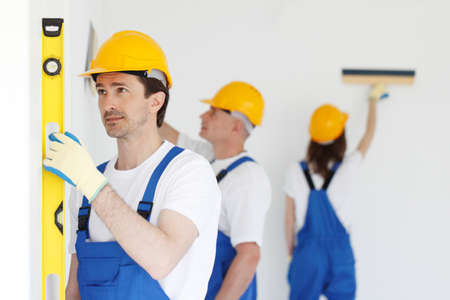 Group of smiling builders in hardhats with tools indoors building, teamwork and people concept Archivio Fotografico