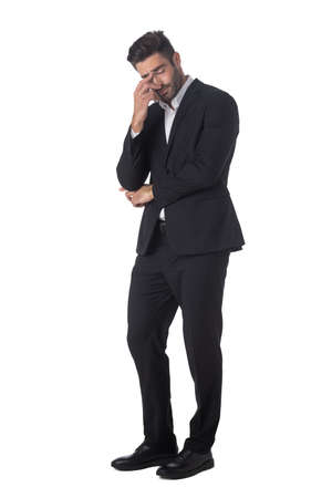 Full length portrait of young handsome business man in black suit feeling stress or depression studio isolated on white background