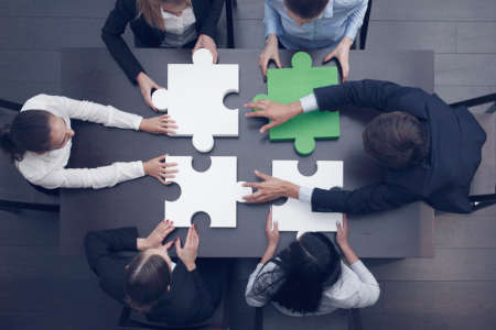 Group of business people assembling jigsaw puzzle at office table, top view, team support and help concept, green and white pieces