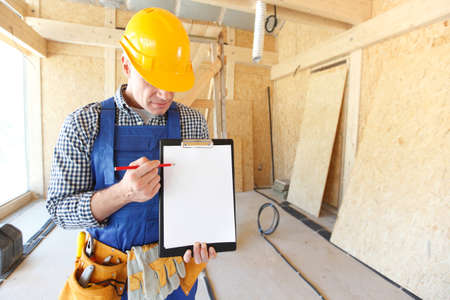Worker showing document at construction site area, blank copy space for text Foto de archivo