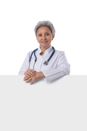 Mature asian doctor holding blank banner isolated on white background