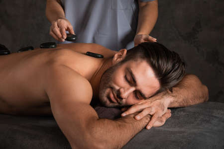 A good-looking man getting hot stone massage lying down at spa