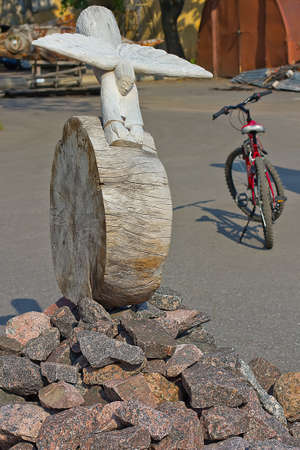 abstract figure of an wooden figure like an angel flying and rolling down from the stone rock with a bicycle against Stock Photo - 13725500