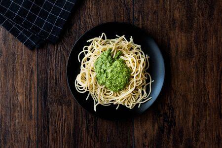 Spaghetti with pesto sauce on dark wooden surface. Organic food.
