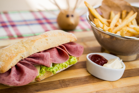 Ham sandwich with fried potatoes, ketchup and mayonnaise.