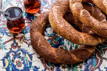 Turkish Bagel Simit with tea on ottoman pattern surface. (ramadan concept)