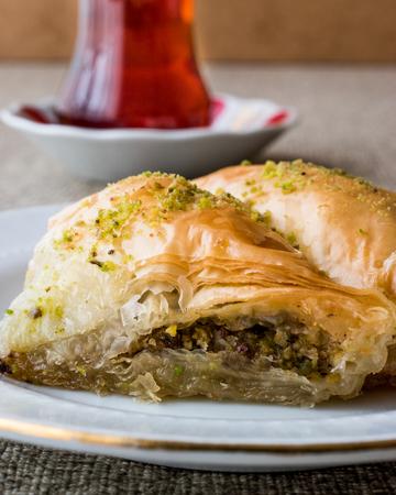Turkish Baklava sobiyet with pistachio and tea. Traditional dessert concept.