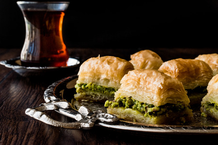 Turkish Dessert Baklava with tea on silver tray. Desset Concept.