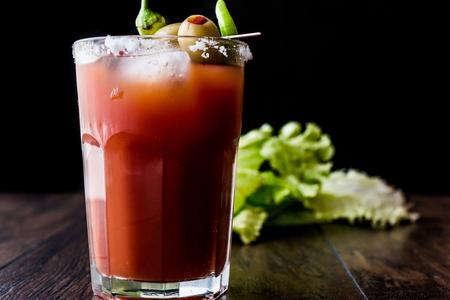 Cóctel Bloody Mary con aceitunas verdes, pimienta, lechuga, sal y hielo. Concepto de bebidas. Foto de archivo - 85014386