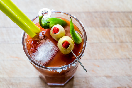 Bloody Mary Cocktail with green olive, pepper, salt and ice. Beverage Concept. Stock Photo