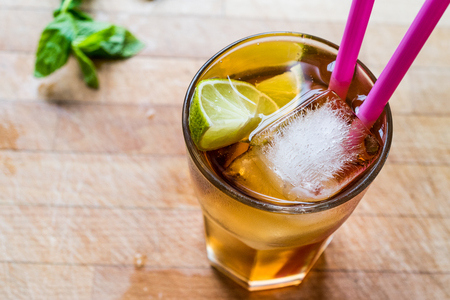 Long island iced tea cocktail with lime, ice and served with pink straw. Beverage concept.