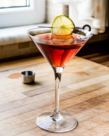 Cosmopolitan Cocktail with lime on wooden surface. Beverage concept. Stock Photo