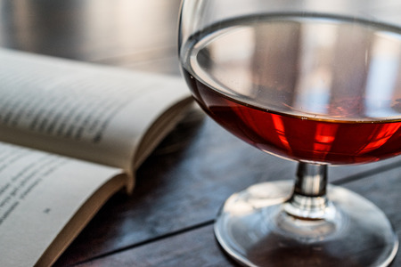 Glass of Cognac with a book on wooden surface. Beverage Concept.