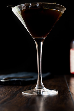 sweet vermouth: Black Manhattan Cocktail with olives on dark wooden surface. Dark Concept. Stock Photo