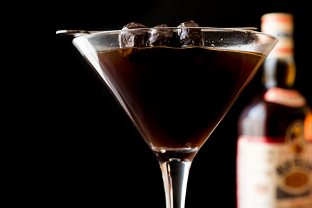 roy: Black Manhattan Cocktail with olives on dark wooden surface. Dark Concept. Stock Photo