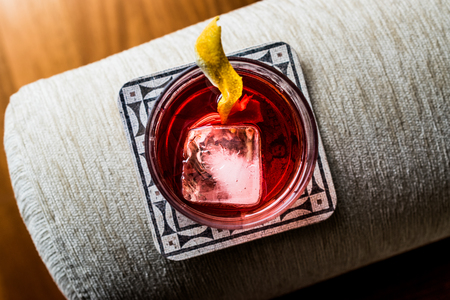 sweet vermouth: Negroni Cocktail with lemon peel and ice. Beverage Concept. Stock Photo
