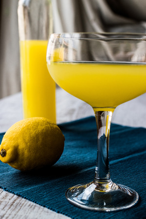 Lemon Liqueur Limoncello with lemon on dark wooden surface. Beverage Concept. Stock Photo