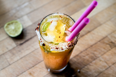 Mexican Michelada Cocktail with beer, lime, ice and spices. Beverage Concept.