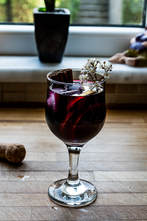 Sangria Cocktail in wine glass with lemon, cinnamon, fruits and ice. Beverage Concept. Stock Photo