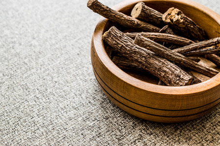 Dried Licorice Sticks in wooden bowl  Meyan Koku. Organic Concept.