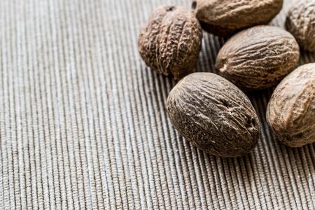 Organic Nutmeg or muskat on fabric surface. Stock Photo