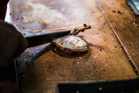 Man is preparing kokorec (fried sheep bowel) with knife on wooden surface. fast food Stock Photo