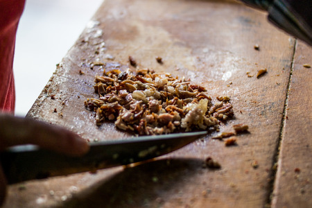 Man is preparing kokorec (fried sheep bowel) with knife on wooden surface. fast food Reklamní fotografie