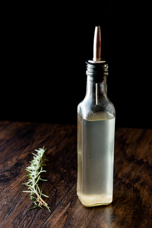 White Vinegar in bottle with rosemary. Organic Food.