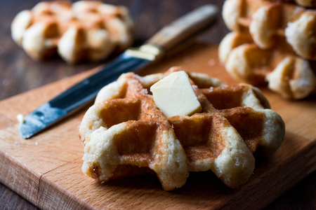 Belgium Waffle with Butter on wooden surface. Traditional Food. Stock Photo
