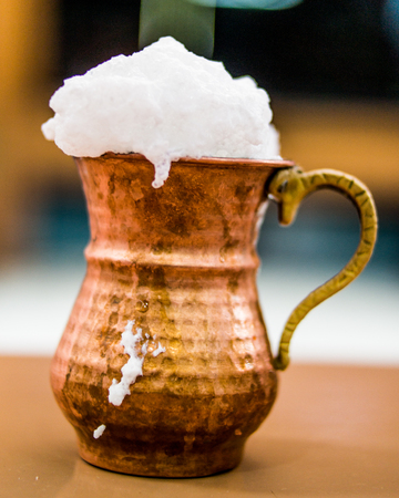Turkish Drink Ayran or Buttermilk with foam in copper cup. beverage concept.