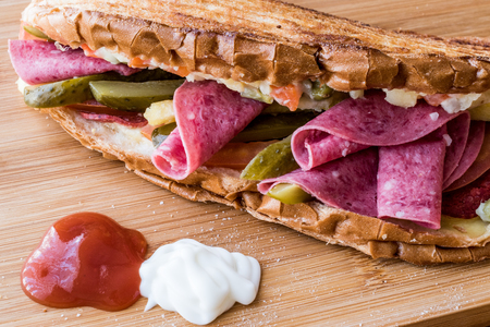 Ayvalik Toast  Salami Sandwich with Russian Salad and pickle on wooden surface