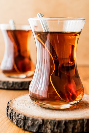 Traditional Turkish tea with spoon on wooden surface (turkish drink)