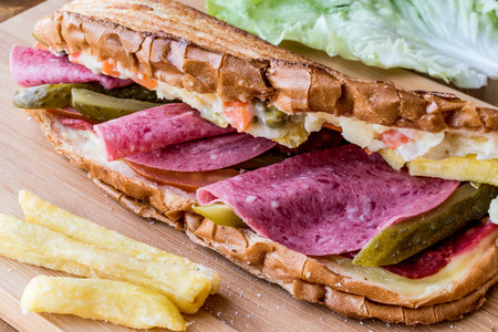Ayvalik Toast  Salami Sandwich with Russian Salad, pickle and potatoe on wooden surface Stock Photo