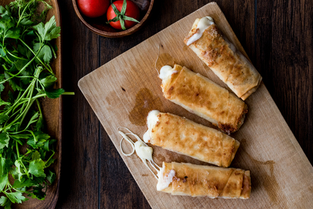 Turkish Pacanga Boregi with pastirma and cheddar (melted) cheese. / Pastirmali Borek on wooden surface 版權商用圖片