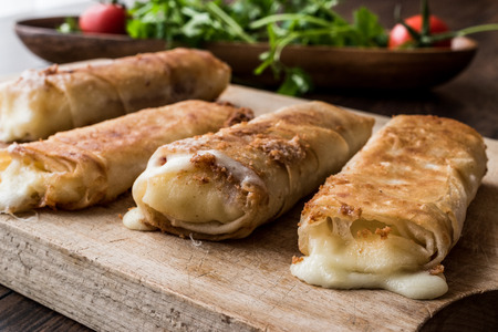 Turkish Pacanga Boregi with pastirma and cheddar (melted) cheese.  Pastirmali Borek on wooden surface Stock Photo