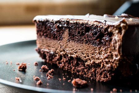 Devils Cake with Chocolate in black plate. Dessert Concept.