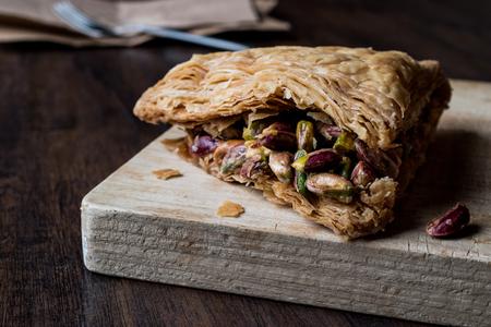 Halep Dessert with Pistachio  Fistikli Baklava on wooden surface Stock Photo