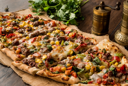 Turkish Pide with meat and vegetables on a wooden surface. Stock Photo