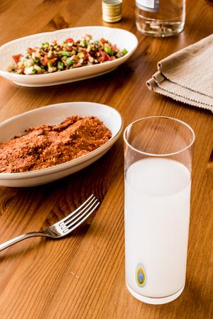 Turkish Drink Raki with acili ezme and gavurdagi salad with walnut. Stock Photo
