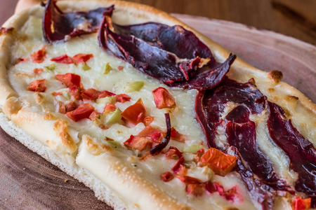 Turkish Pide with Pastirma , tomato and melted cheese on a wooden surface. Stock Photo
