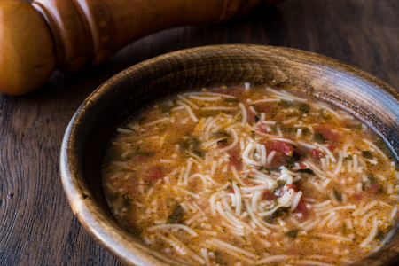 Turkish Traditional Vermicelli Soup / Tel sehriye corbasi on a wooden surface.