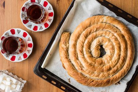 Round Borek in tray  Greek Cheese pie on wooden surface