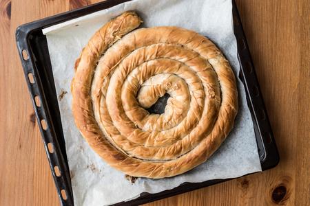 Round Borek in tray / Greek Cheese pie on wooden surface Foto de archivo
