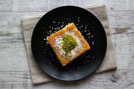 Turkish Dessert Revani with pistachio powder in a black plate.